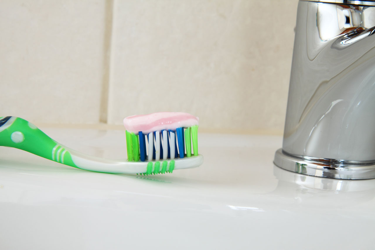 toothbrush with toothpaste on it near faucet